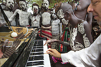 """Ethiopia. Southern Nations, Nationalities, and Peoples' Region. Omo Valley. Korcho Village. Kara tribe. Agro-pastoralist group. The Kara men are best known for the elaborate body painting they indulge in before important ceremonies. They paint their faces and bodies in white chalk. Marc Vella is a french musician and a nomadic pianist. Over the last 25 years he has travelled with his Grand Piano in around forty countries to celebrate humanity. Thanks to the variacordes which he has devised, his piano music is unique. Creator of """"La Caravane amoureuse"""" (The Caravan of Love) he takes people with him to say """"I love you"""" to others and """"lovingly conquered"""" their hearts and souls. Marc Vella and a Karo boy play an improvised duet-playing - one piano and four hands. The Omo Valley, situated in Africa's Great Rift Valley, is home to an estimated 200,000 indigenous peoples who have lived there for millennia. Amongst them are 1,000 to 2,000 Karo who dwell on the eastern banks of the Omo river. Southern Nations, Nationalities, and Peoples' Region (often abbreviated as SNNPR) is one of the nine ethnic divisions of Ethiopia. 8.11.15 © 2015 Didier Ruef"""