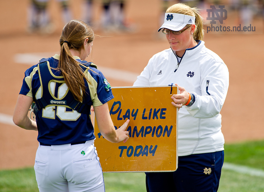May 4, 2013; Associate Softball coach Kris Ganeff holds the 'Play Like A Champion Today' sign for catcher Amy Buntin before a game...Photo by Matt Cashore/Univeristy of Notre Dame