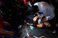"""A medic attempts to revive a protester who was shot as gunshots ring out. """"Red shirt"""" protesters taunted the Thai military as they retreated at the Democracy monument in central Bangkok. More than 20 people were killed during the clashes as the army opened fire with live ammunition, tear gas and rubber bullets. A handful of soldiers also died and ane journalist was shot dead. The army withrew leaving 6 armoured personnel carriers and two Humvees which were then vandalised by the protesters. They also deserted the drivers of the vehicles. They were nearly linched by an angry crowd but later rescued by """"red Shirt"""" organisers."""