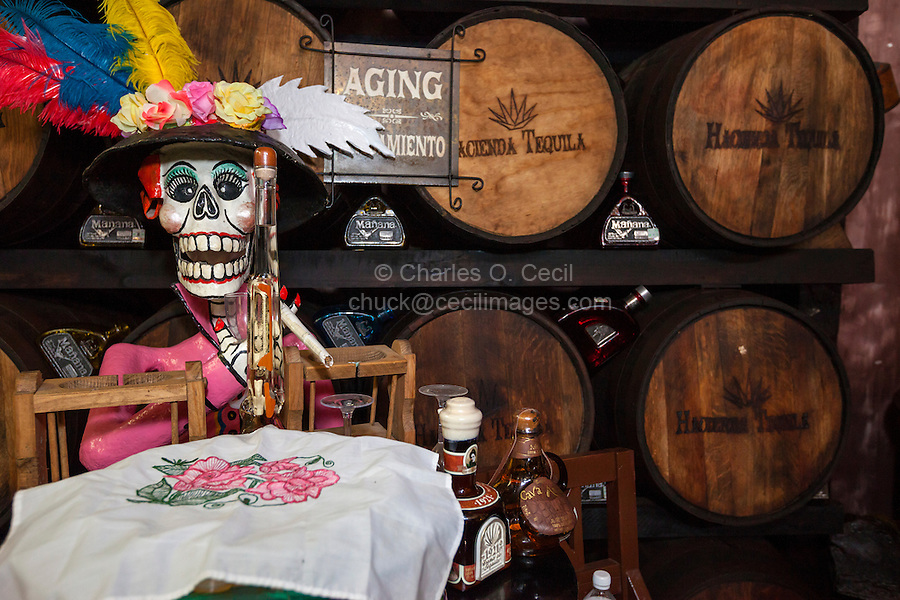 Catrina Skeleton Figure on Display by Aging Barrels of Tequila, Tequila Museum, Playa del Carmen, Riviera Maya, Yucatan, Mexico.