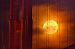 December full moon set behind the Golden Gate Bridge.