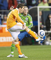 Houston Dynamo defender Hunter Freeman kicks the ball away from Seattle Sounders FC midfielder Erik Friberg  during play at Qwest Field in Seattle Friday March 25, 2011. The match ended in a 1-1 draw.