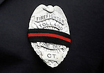 Badges with a mourning band worn by all the firefighters like this one belonging to Tolland Firefighter Glenn Vincent, during the funeral for Hartford firefighter Kevin Bell, Monday, Oct 13, 2014, at the First Cathedral, in Bloomfield, Bell was killed in a house fire last week in Hartford. (AP Photo / Journal Inquirer, Jim Michaud)