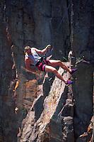 Rock climber rappelling at Minnesota's Palisade Head along the Lake Superior shoreline.