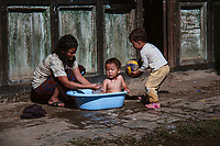 A mother bathes her toddler child while his young brother offers his football. Every day life behind Punakha Dzong, Bhutan
