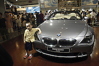A boy poses for a photo besides a BMW 645Ci Cabrio at the Auto China 2004 exhibition in Beijing, China..