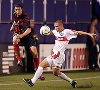The MetroStars' Mark Lisi sends a ball up field as the Chicago Fire's Logan Pause attempts a tackle. The Chicago Fire played the NY/NJ MetroStars to a one all tie at Giant's Stadium, East Rutherford, NJ, on May 15, 2004.