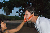 Mato Grosso State, Brazil. Aldeia Metuktire (Kayapo). Patrick Cunningham receiving urucum face paint.