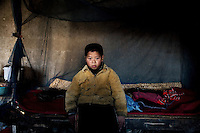 Fan Lu Yang, 10, sits on his bed in his grandparents' home in Fanzhuang Village, Gangyun County, Jiangsu, China.  Fan Lu Yang lives with grandfather Fan Qing Huai and grandmother Wang Bao Ying.  The grandparents are both over 75 and often ill, and the income from growing corn, wheat, and hay, cannot support the three.  Fan Lu Yang's father died in 2000 in an accident at a small coal mine and his mother developed dementia and disappeared about a year before this picture was taken...At the time of the picture, China's Amity Foundation charity, was investigating the family's situation in preparation to raise money to financially support these children and other orphans in similar situations.  With Amity's support, each orphan, aged 6-12, would receive approximately 1,400 RMB annually (about 200 USD) to pay for the cost of living. Amity works to keep children out of the institutional orphanages in China, preferring to provide monetary assistance that can help maintain a family environment for the orphans it helps.