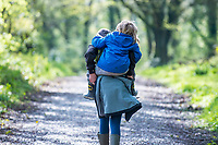 A young boy has a piggy back as they walk through woodland at Canaston Bridge, Pembrokeshire