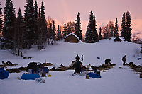 Teams rest as the sun hits Wolverine Mountain behind Winter Lake Lodge at the Finger Lake checkpoint during Iditrod 2008