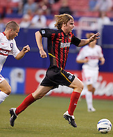 The  MetroStars' Eddie Gaven is chased by  Chicago Fire's Logan Pause. The Chicago Fire played the NY/NJ MetroStars to a one all tie at Giant's Stadium, East Rutherford, NJ, on May 15, 2004.