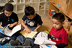 Preschool Headstart 3-5 year olds group of three boys sitting separately looking at books parallel play horizontal