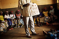 A health district advisor holds a meeting with pregnant women to explain the risks and implications of malaria, and how to treat it. He advises them not to resort to traditional village doctors if they are suffering from a fever that might be caused by malaria...