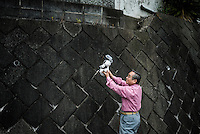 Kouzaburo Sakurai holds an AIBO while his wife Michiko Sakurai (not shown) photographs it near their home in Tokyo.  In 1999, Sony released a series of robotic pets called AIBO or Artificial Intelligence Robot. In 2006, they discontinued the AIBO line and then in 2014, discontinued all reparair services on the AIBO. A small community of AIBO owners still exists and a new repair service has emerged to help keep the AIBOs running.