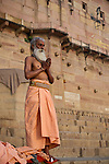 Indian man praying on the ghats at the Ganges River in Varanasi, Uttar Pradesh, India