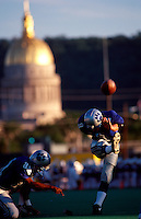Blurred motion image of a high school kicker as he connects with the football as the captitol dome glows in the background. Charleston, West Virginia.