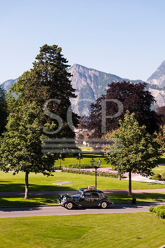 Switzerland. Vintage pre-war Citroen car with luggage rack in park by mountains.