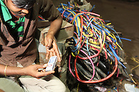 A man checks his cellphone in the Chandni Chowk electronics market in Kolkata, India. November, 2013