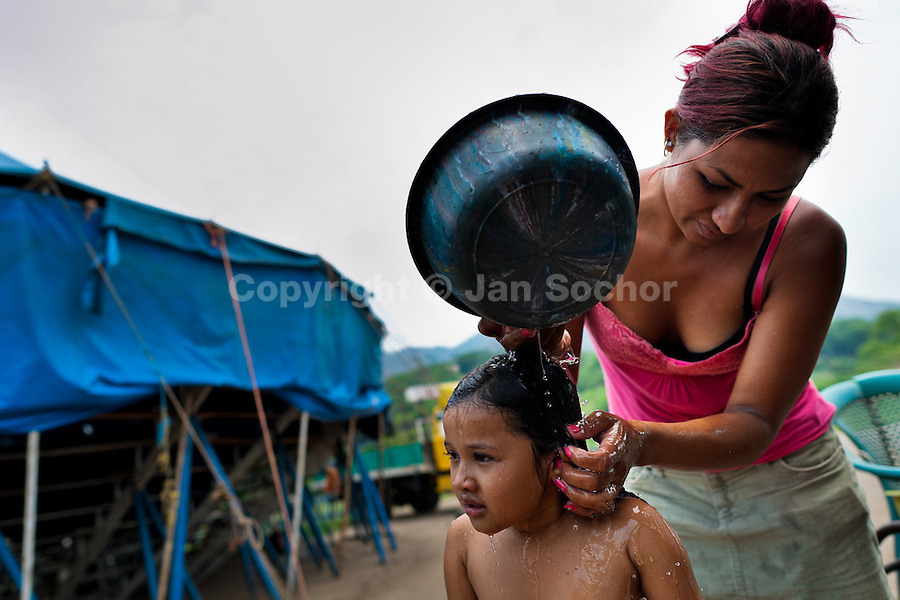 A Salvadorean girl is given a bath in front of the tent of the Circo Brasilia, a family run circus travelling in Central America, 10 May 2011. The Circo Brasilia circus belongs to the old-fashioned traveling circuses with a usual mixture of acrobat, clown and comic acts. Due to the general loss of popularity caused by modern forms of entertainment such as movies, TV shows or internet, these small family enterprises balance on the edge of survival. Circuses were pushed away and now they have to set up their shows in more remote villages. The circus art and culture is slowly dying in Latin America.