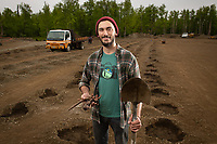 UAA Environment and Society Junior Nicolas Donatelli holds a peony root cutting and shovel as he and his hired hands prepare to plant his first crop of the flowers in Palmer. Donatelli is among a growing number of Alaskan entrepreneurs seeking to capitalize on the high demand for peonies for weddings and Alaska's favorable growing conditions for the flowers.