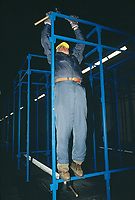 Switzerland. Canton Lucerne. A man holding a hammer and waering a yellow helmet builds bunk beds in the Sonnenberg tunnel in Lucerne during the largest civil defense exercise ever held in the country. From 16 to 21 November 1987, almost 1200 men and women converted a motorway tunnel into perhaps the world's largest bunker structure. The civil protectors had to prove during the exercise «Ameise » ( Ants in english) that in an emergency more than 20,000 inhabitants of the city of Lucerne could survive here in the mountain for two weeks. The Sonnenberg Tunnel is a 1,550 m  long motorway tunnel, constructed between 1971 and 1976. At its completion it was also the world's largest civilian nuclear fallout shelter, designed to protect 20,000 civilians in the eventuality of war or disaster. Based on a federal law from 1963, Switzerland aims to provide nuclear fallout shelters for the entire population of the country. The construction of a new tunnel near an urban centre was seen as an opportunity to provide shelter space for a large number of people at the same time. The giant bunker was built between 1970 and 1976 at a cost of 40 million Swiss francs. The shelter consisted of the two motorway tunnels (one per direction of travel), each capable of holding 10,000 people in 64 person subdivisions. A seven story cavern between the tunnels contained shelter infrastructure including a command post, an emergency hospital, a radio studio, a telephone centre, prison cells and ventilation machines. The shelter was designed to withstand the blast from a 1 megaton nuclear explosion 1 kilometer away. The blast doors at the tunnel portals are 1.5 meters thick and weigh 350 tons. The logistical problems of maintaining a population of 20,000 in close confines were not thoroughly explored, and testing the installation was difficult because it required closing the motorway and rerouting the usual traffic. The only large-scale test, a five-day exercise in 1987 to practice converting the