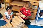 Education Preschool first days of school boy and girl working together on block construction