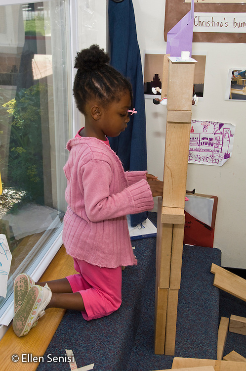 MR / College Park, Maryland.Center for Young Children, laboratory school within the College of Education at the University of Maryland. Full day developmental program of early childhood education for children of faculty, staff, and students at the university..Girl (5, African American) builds block structure during free time..MR: Tho16.© Ellen B. Senisi