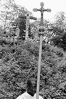 Switzerland. Canton Schwyz. Einsiedeln. African pilgrimage. Various religious african communities coming from allover Switzerland and southern Germany celebrate their faith and belief in Jesus Christ. A black man carries a wooden cross with the crucifixion of Jesus Christ. Jesus, whom Christians believe to be the Son of God as well as the Messiah, was sentenced to be crucified. Collectively referred to as the Passion, Jesus' redemptive suffering and death by crucifixion represent the central aspects of Christian theology, including the doctrines of salvation and atonement. 31.08.13 © 2013 Didier Ruef