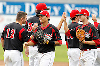 Batavia Muckdogs first baseman Romulo Ruiz #23 and Danny Stienstra #2 high five teammates including Jeremy Patton #12 after a game against the Auburn Doubledays at Dwyer Stadium on September 4, 2011 in Batavia, New York.  Batavia defeated Auburn 4-2.  (Mike Janes/Four Seam Images)