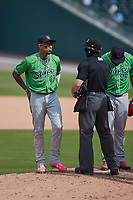 Home plate umpire Chris Marco chats with Gwinnett Stripers third baseman Johan Camargo (17) during the game against the Charlotte Knights at Truist Field on May 9, 2021 in Charlotte, North Carolina. (Brian Westerholt/Four Seam Images)