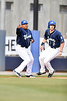 Asheville Tourists manager Robinson Cancel (37) gives signals as Casey Golden (11) rounds third base during a game against the Columbia Fireflies at McCormick Field on April 14, 2018 in Asheville, North Carolina. The Fireflies defeated the Tourists 7-6. (Tony Farlow/Four Seam Images)