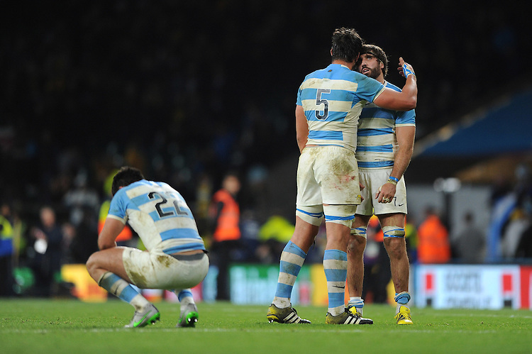 Juan Martin Fernandez Lobbe of Argentina looks stunned as he is comforted by Tomas Lavanini of Argentina and team mate Jeronimo de la Fuente of Argentina crouches at the end of the Semi Final of the Rugby World Cup 2015 between Argentina and Australia - 25/10/2015 - Twickenham Stadium, London<br /> Mandatory Credit: Rob Munro/Stewart Communications