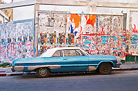 A classic but run down blue and white old American car parked in a street in the city against a background of a wall full with political and publicity posters Montevideo, Uruguay, South America