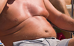 Over weight male obesity with plastic cup of red wine sunbathing Wimbledon town, London, UK
