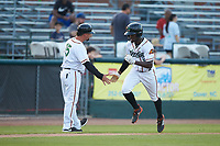 Eric Jenkins (5) of the Down East Wood Ducks slaps hands with third base coach Steve Mintz (15) as he rounds the bases after hitting a home run against the Winston-Salem Dash at Grainger Stadium Field on May 17, 2019 in Kinston, North Carolina. The Dash defeated the Wood Ducks 8-2. (Brian Westerholt/Four Seam Images)