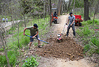 Dustin Fairbanks (from left) and David Greer spread soil, Monday, April 5, 2021 along the bike path at the Art Trail in Bentonville. NWA Trailblazers added soil to patches along the bike path to reduce erosion, improving the way water flows through the trail. Check out nwaonline.com/210406Daily/ for today's photo gallery. <br /> (NWA Democrat-Gazette/Charlie Kaijo)