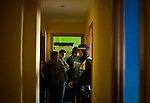 Ecuadorian homeowner Nelson Castillo (C) stands on March 13, 2012 in his house in Madrid as police arrive to evict him. Spain on March 9 approved a new voluntary 'code of conduct' for banks which aims to help poor homeowners settle their debts and reduce a wave of evictions brought on by the economic crisis. Spanish banks currently seize the homes of those who default on their mortgages and often demand further payment from those evicted if the value of the house has fallen below that of the loan. The new rules will apply in cases where every member of a household is unemployed and mortgage payments are equal to more than 60 percent of their income. (C) Pedro ARMESTRE