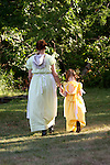 A mother and daughter walking together in prairie dresses outside