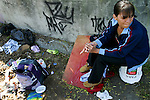 A woman sits with a used needle in her hand after injecting herself with a  fix of morphine mixed with cocaine and synthetic heroin in a vacant lot along Mason Street in Victoria, B.C. The vacant lot, littered with garbage and used needles, is a common site for intravenous drug users to utilize as a shooting gallery. Photo shot for the GLOBE and MAIL.