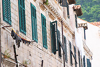 An old house with green window shutters and clothes lines with washed clothes drying Dubrovnik, old city. Dalmatian Coast, Croatia, Europe.