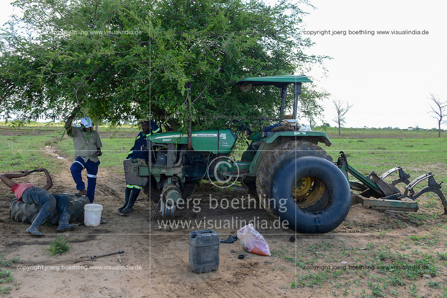 ZAMBIA, Mazabuka, Chikankata area, medium scale farmer Stephen Chinyama with John Deere Tractor, patching a flat tube of a tire at the field
