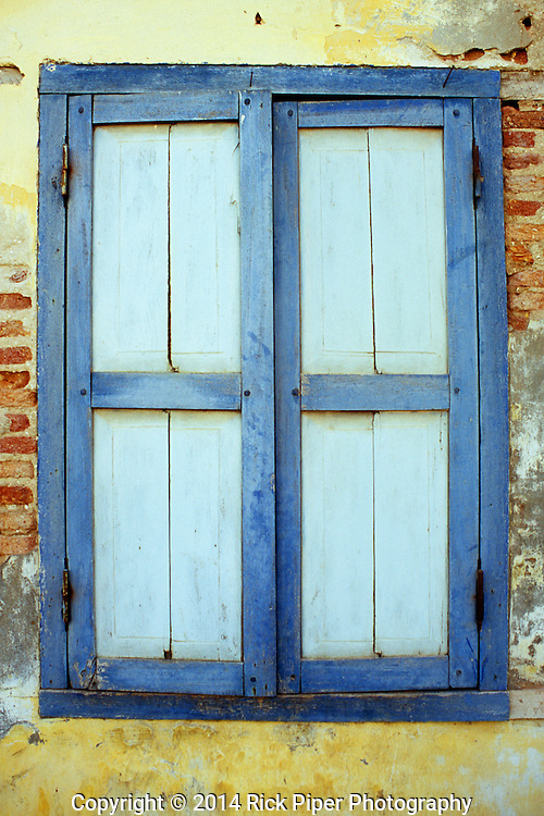 Closed blue painted wooden window shutters in weathered decaying old French colonial building, Kampot, Cambodia.