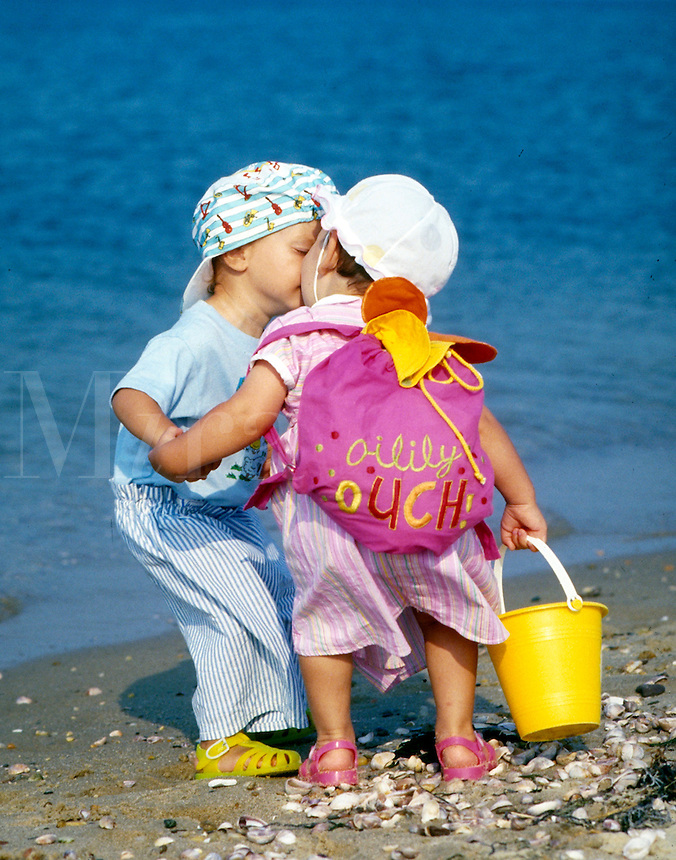 Two toddlers kissing on the beach.