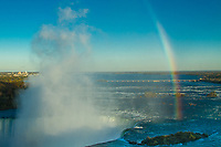 Amazing Niagara Falls horseshoe in morning light with mist, a beautiful rainbow, and the upstream river in the background, Ontario Canada