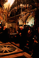 Monks and pilgims kneel in prayer in the Armenian Orthodox Church of the Sepulchre. Jerusalem, Israel.