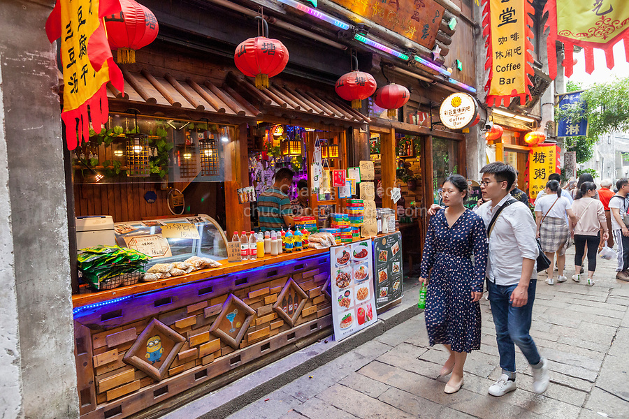 Suzhou, Jiangsu, China.  Chinese Couple Passing a Coffee Bar on Shantang Street, a Historic District.