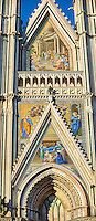 Close up of the main door with mosaics created between 1350 and 1390 after designs by artist Cesare Nebbia  on the14th century Tuscan Gothic style facade of the Cathedral of Orvieto, designed by Maitani, Umbria, Italy