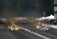 Aug. 3, 2013; Kent, WA, USA: NHRA funny car driver Tony Pedregon (right) races alongside Jeff Arend during qualifying for the Northwest Nationals at Pacific Raceways. Mandatory Credit: Mark J. Rebilas-USA TODAY Sports