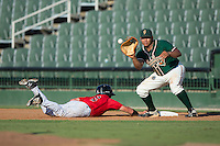 Josh Naylor (10) of the Greensboro Grasshoppers waits for a pick-off throw as Alex Call (2) of the Kannapolis Intimidators dives back towards first base at Intimidators Stadium on July 17, 2016 in Greensboro, North Carolina.  The Grasshoppers defeated the Intimidators 5-4 in game two of a double-header.  (Brian Westerholt/Four Seam Images)